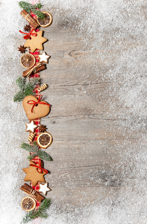 christmas spices: Christmas background with cookies, fir branches and spices on the old grunge wooden board Stock Photo