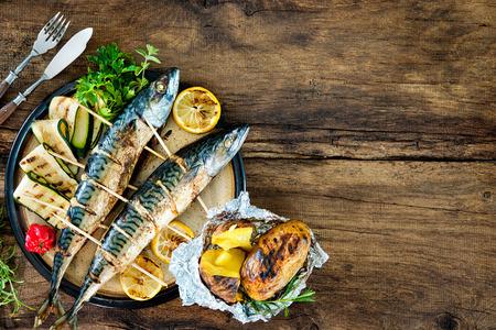 Gegrilde makreel vis met gebakken aardappelen op houten tafel Stockfoto