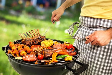 남자 가족의 저녁 식사를 위해 바베큐 고기 요리 스톡 콘텐츠