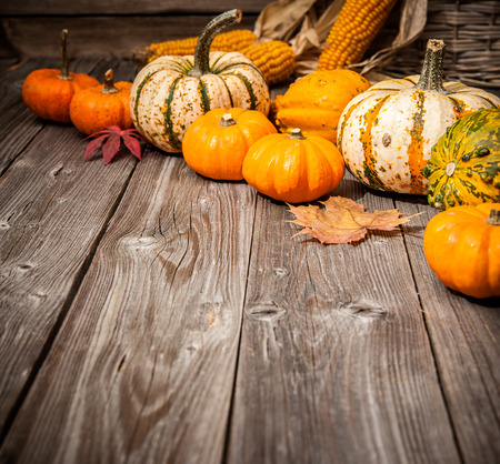 country life: Autumn still life with pumpkins and leaves on old wooden background