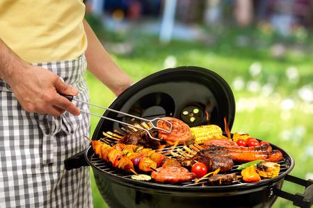 chorizos asados: Hombre que cocina la carne en barbacoa para cena familiar