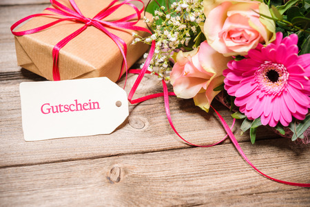 Bunch of flowers, gift box and tag with German text coupon on wooden background