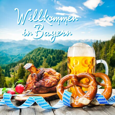 wiesn: Roasted pork knuckle with pretzels and beer. Background with German text Welcome in Bavaria