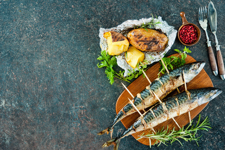 hot stone: Grilled mackerel fish with baked potatoes on stone background