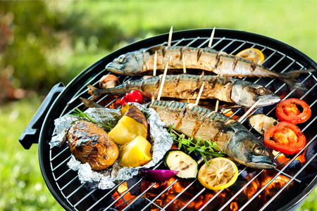Gegrilde makreel vis met gebakken aardappelen over de kolen op een barbecue Stockfoto