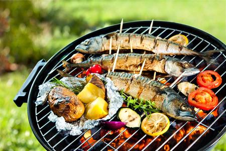 brochetas de frutas: Pescados de la caballa a la plancha con papas al horno en los carbones en una barbacoa Foto de archivo