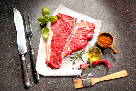 seasoning: Raw fresh meat T-bone steak and seasoning on dark background Stock Photo