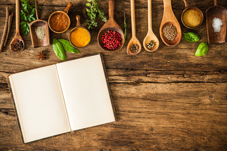 food additives: Blank cookbook and spices on wooden table
