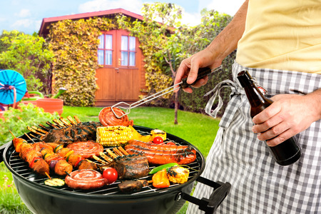 Man cooking meat on barbecue in front of backyard