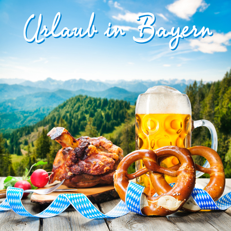 wiesn: Roasted pork knuckle with pretzels and beer. Background with German text Holidays in Bavaria