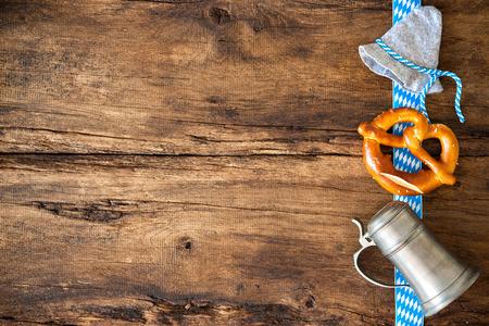 オクトーバーフェスト ビール ジョッキ、プレッツェルとバイエルンの帽子と祭りの背景 写真素材