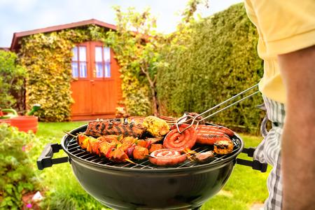 parrillero: Hombre que cocina la carne en barbacoa en frente de patio trasero