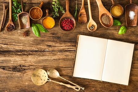 cocineras: Libro de cocina en blanco y especias en la mesa de madera Foto de archivo
