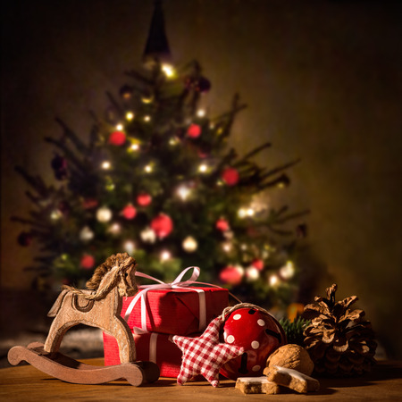 antique background: Gifts and decorations with Christmas tree in background