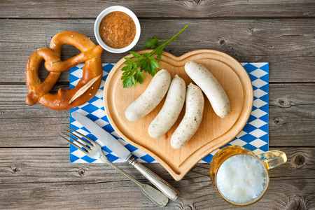 scalded sausage: Bavarian meal with white sausage on cutting board
