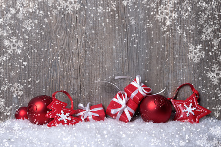 Christmas decorations and gift boxes on snow-covered wooden background