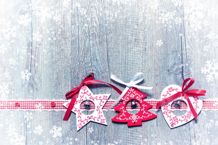 Christmas decorations on snow-covered wooden background
