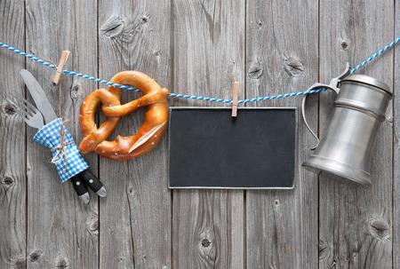Message, beer mug and pretzel hanging on the clothesline against wooden board. Background for Oktoberfest