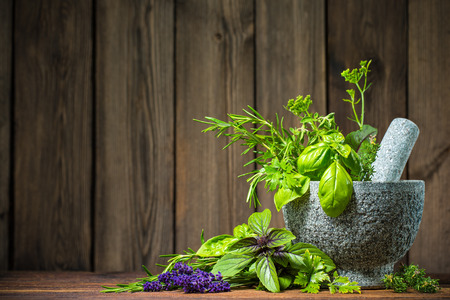 Mortar with herbs on wooden table