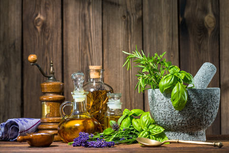 organic plants: Mortar with herbs and oil on wooden table