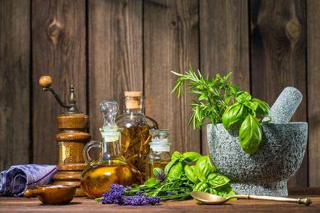 mortero: Mortero con hierbas y aceite de mesa de madera Foto de archivo