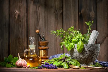 aceite de cocina: Mortero con hierbas y aceite de mesa de madera Foto de archivo