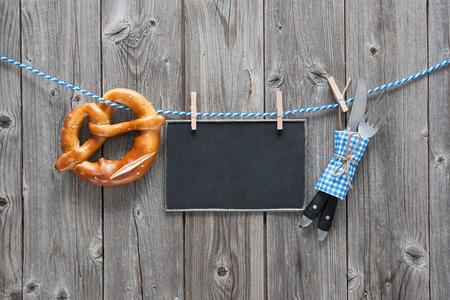 メッセージ、カトラリー セット、木製基板に対して物干し用ロープにぶら下がっているプレッツェル。オクトーバーフェストの背景