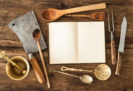 cocina antigua: Cuaderno vacío o libro de cocina y utensilios de cocina de la vendimia en la mesa de madera