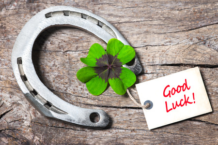 fourleaved: Horseshoe, Leafed clover and tag with good luck on wooden board Stock Photo
