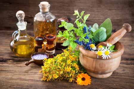 mortero: Aceite esencial, mortero con hierbas frescas y sal de baño sobre fondo de madera