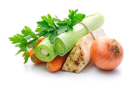 Mirepoix. Ingrediënten voor groente bouillon, wortelen, uien, prei, selderij, peterselie op een witte achtergrond Stockfoto