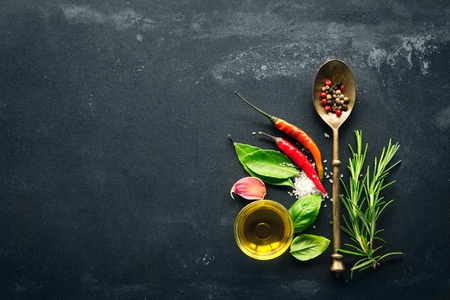 Herbs and spices with old metal spoon on slate background