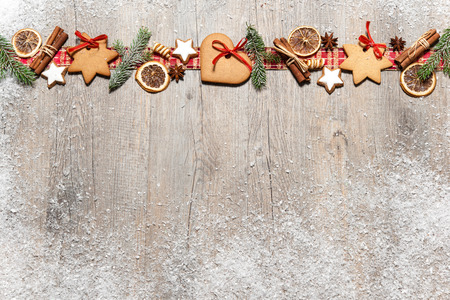 Christmas background with cookies, fir branches and spices on the old grunge wooden board Imagens