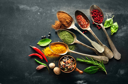 Various herbs and spices on black stone plate Banco de Imagens