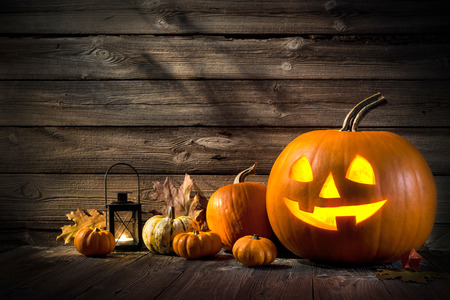 Halloween pumpkin head jack lantern on wooden background Imagens