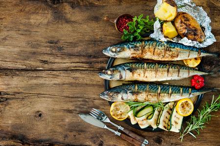 brochetas de frutas: Pescados de la caballa a la plancha con papas al horno en mesa de madera Foto de archivo