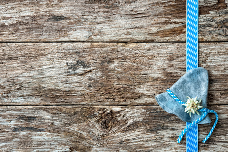 menu background: Bavarian hat with edelweiss and ribbon on weathered wood background