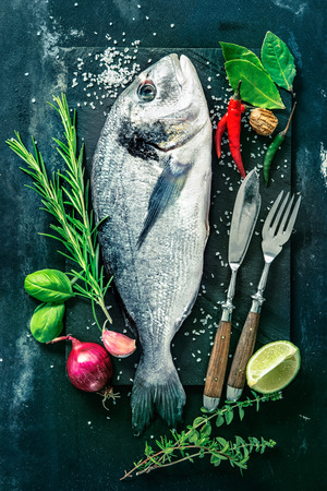 fish plate: Fresh Gilt-head bream with spices and seasoning on slate plate Stock Photo