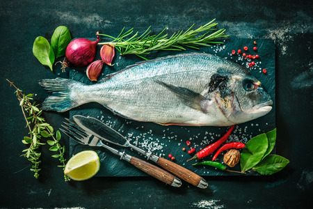 raw fish: Fresh Gilt-head bream with spices and seasoning on slate plate Stock Photo