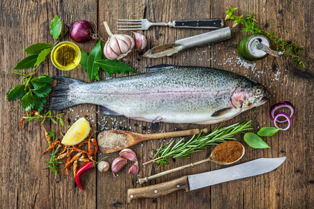 Fresh trout with spices and seasoning on cutting board Stockfoto
