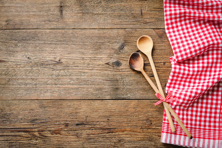 tablecloth: Kitchenware on wooden table with a red checkered tablecloth