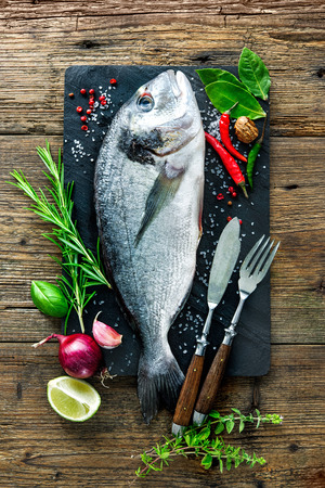 gilthead bream: Fresh Gilt-head bream with spices and seasoning on slate plate Stock Photo