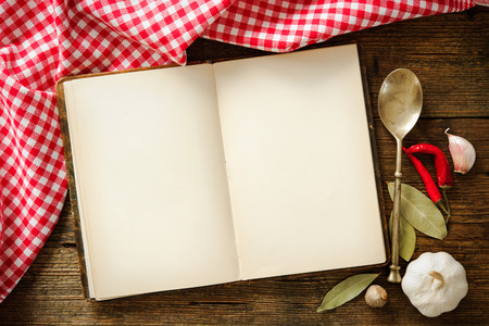 Open cookbook with kitchenware on checkered tablecloth Stockfoto