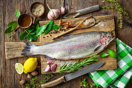 restaurant kitchen: Fresh trout with spices and seasoning on cutting board Stock Photo
