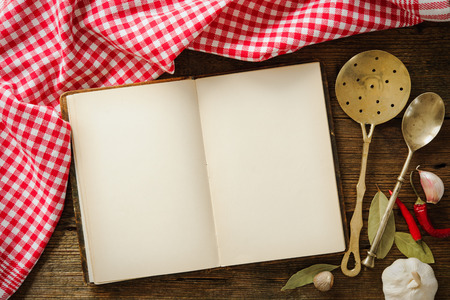 blank page: Open cookbook with kitchenware on checkered tablecloth Stock Photo