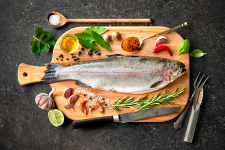 fish plate: Fresh trout with spices and seasoning on cutting board Stock Photo