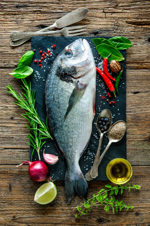 grilled vegetables: Fresh Gilt-head bream with spices and seasoning on slate plate Stock Photo