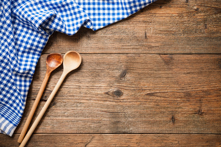 Kitchenware on wooden table with a blue checkered tablecloth