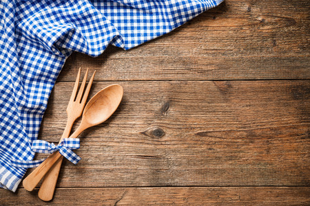 tablecloth: Kitchenware on wooden table with a blue checkered tablecloth