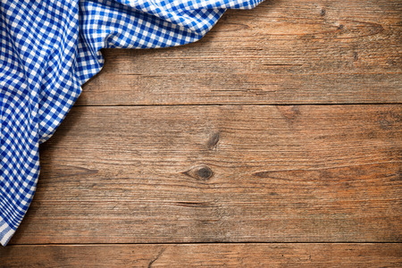 checker: Blue checkered tablecloth on wooden table Stock Photo